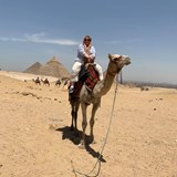Kathy on a camel at the pyramids